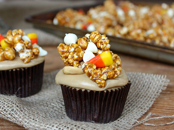 Caramel Corn Cupcakes for Halloween - caramel cupcakes topped with caramel frosting and caramel popcorn studded with candy corn and cashews   by Lauren Kapeluck for TheCakeBlog.com