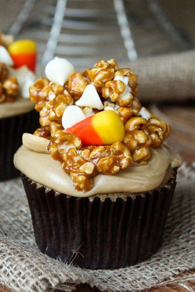 Caramel Corn Cupcakes for Halloween - caramel cupcakes topped with caramel frosting and caramel popcorn studded with candy corn and cashews | by Lauren Kapeluck for TheCakeBlog.com