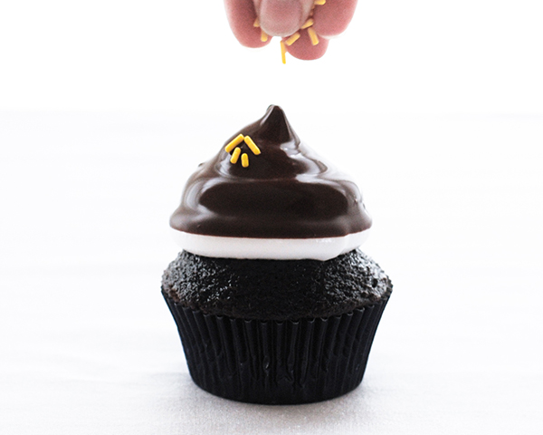 NFL Game Day Cupcakes   chocolate cupcakes with fluffy marshmallow frosting and dipped in chocolate. Perfect for football tailgating and homegating.