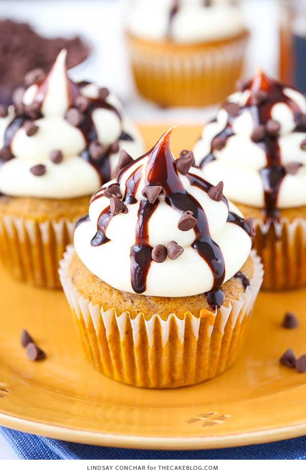 Pumpkin Chocolate Chip Cupcakes - pumpkin cupcakes studded with chocolate chips, topped with cream cheese frosting and chocolate sauce | by Lindsay Conchar for TheCakeBlog.com