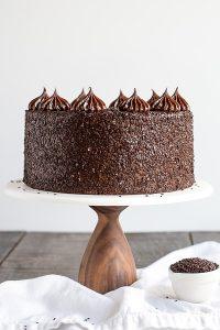 Chocolate Truffle Cake - a chocolate layer cake recipe with dense, moist chocolate cake, silky chocolate truffle frosting and chocolate flakes | by Olivia Bogacki for TheCakeBlog.com