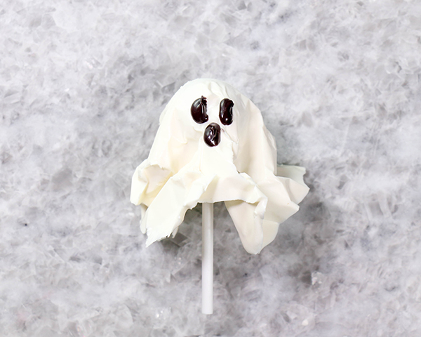 Chocolate Lollipop Ghosts - how to make edible lollipop ghosts for Halloween cakes and cupcakes using white chocolate and suckers | by Erin Gardner for TheCakeBlog.com