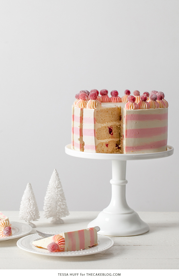 Cranberry Orange Spice Cake - orange cake studded with cranberries topped with white chocolate orange frosting in festive pink and white buttercream stripes | by Tessa Huff for TheCakeBlog.com