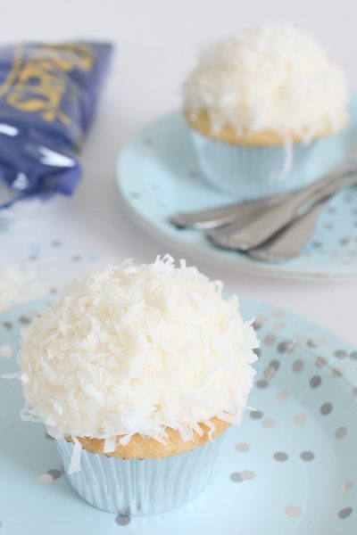 Coconut Cupcakes - fluffy coconut cupcakes made with coconut milk and topped with smooth coconut buttercream and coconut flakes | by ellenJAY for TheCakeBlog.com
