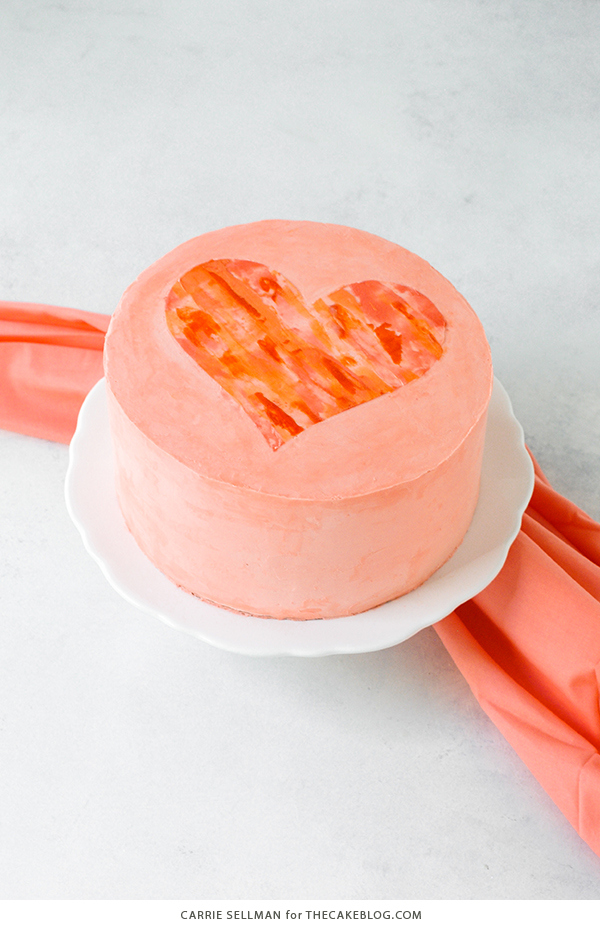Watercolor Heart Cake - how to paint a watercolor heart cake using buttercream frosting and a parchment paper stencil   by Carrie Sellman for TheCakeBlog.com