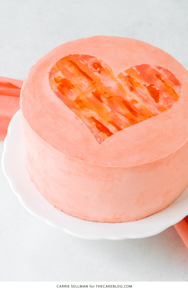 Watercolor Heart Cake - how to paint a watercolor heart cake using buttercream frosting and a parchment paper stencil | by Carrie Sellman for TheCakeBlog.com