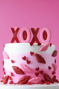 XOXO Valentine's Day Cake - how to make a pink ombre striped cake decorated with chocolate lips, hearts and an XOXO topper | by Cakegirls for TheCakeBlog.com